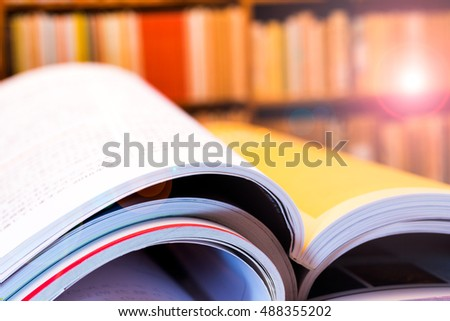 Piles of books and magazines on background of book shelf, with lens flare