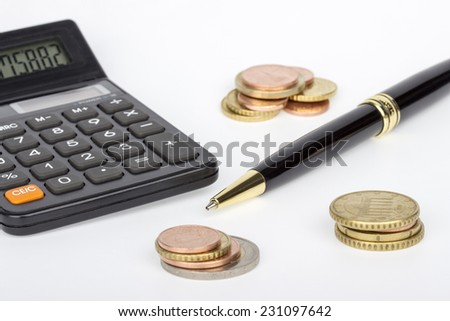 Piles of coins with calculator and pen on a white background - stock photo