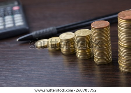Piles of coins with calculator and pen on a wooden background. Business composition. Business concept. Financial close-up background.  - stock photo