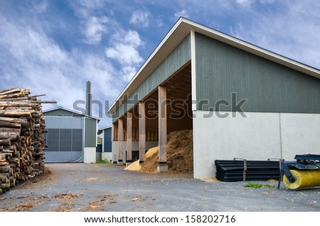 Piles of logs and wood chips waiting to be turned into biofuel for heating  - stock photo