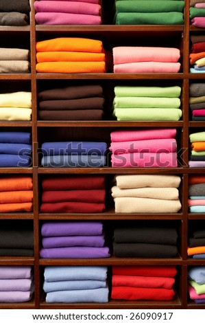 Piles of multicolored knitted woolen clothing - stock photo