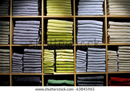 Piles of multicolored towels on the shelves in a shop.