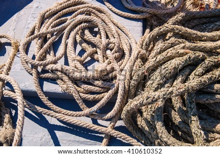 Piles of old strong ropes on wooden boat - stock photo