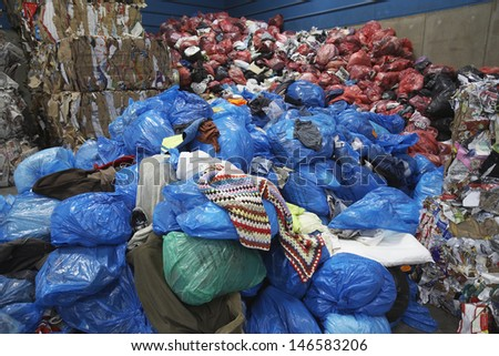 Piles of rubbish bin bags at recycling plant - stock photo