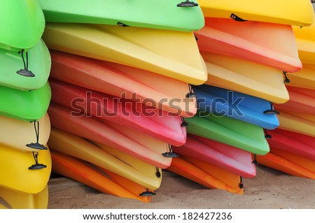 Piles of sherbet colored kayaks put away for the winter in Provincetown - stock photo