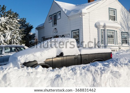 Piles of snow bury a truck and home in a North American suburb. - stock photo