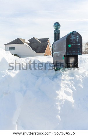 Piles of snow bury the mail box of a modern single family house after blizzard and snow drifts - stock photo