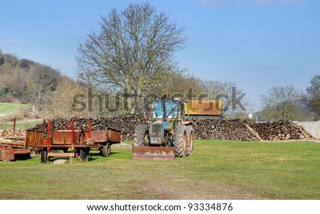 Piles of Timber stacked in a field with Tractor and rusting trailer