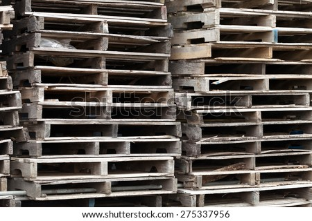 Piles of wooden pallets ready for breaking up and recycling into firewood kindling or DIY projects. - stock photo