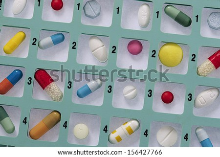 Pill and pill container weekly pillbox - stock photo
