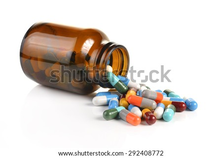Pill bottle spilling pills on to surface isolated on a white background. - stock photo