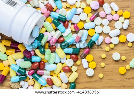 Pill bottle spilling pills on to surface wooden background. View from the top use for background