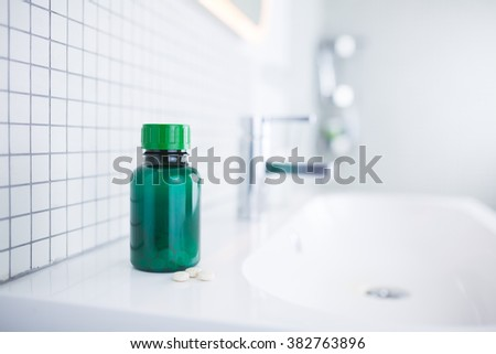 pill bottle standing in the bathroom - stock photo