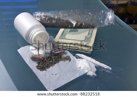 pill bottle with marijuana, cocaine, weed and drug money on a glass table - stock photo