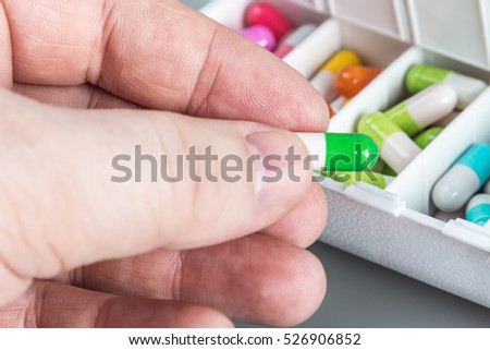Pill in hand on the background of the box with pharmaceuticals