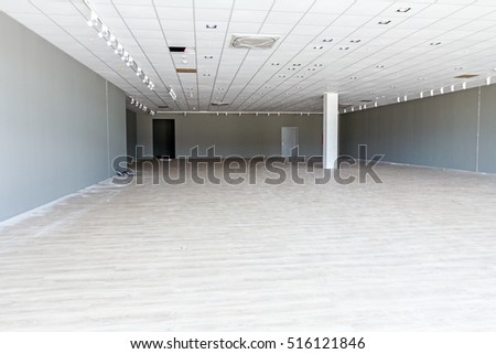 Pillar in empty big room, interior with beige wooden laminate floor and painted walls, Architecture concept