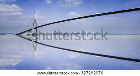 "pillar of the bridge ""Pont du Normandie"" reflected in the Seine river at Le Havre, France - stock photo"