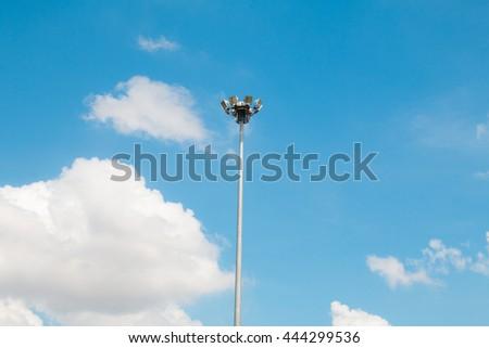 Pillar spotlights high on the blue sky - stock photo