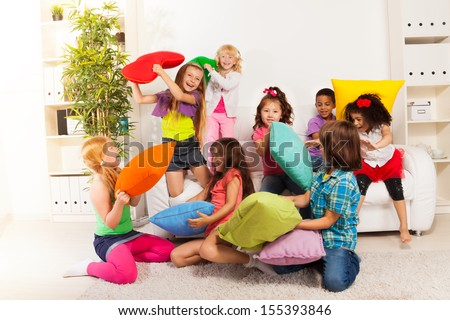 Pillow fight - large group of kids, boys and girls playing in the living room hitting each other with colorful pillows - stock photo