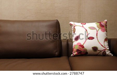 Pillow on a leather sofa - home interiors - stock photo