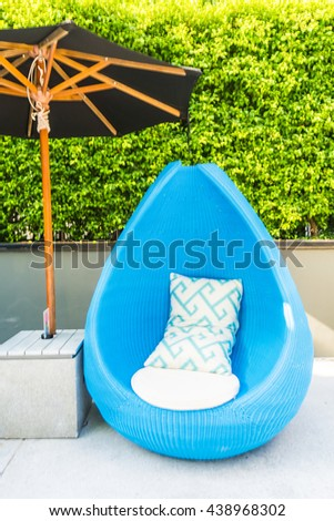 Pillow on chair with umbrella decoration at outdoor patio - stock photo