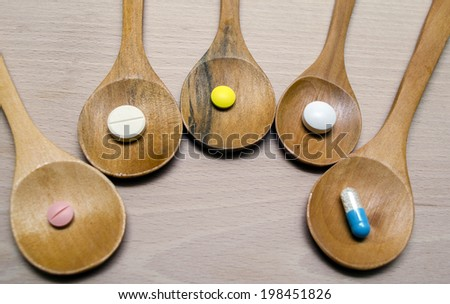 Pills and capsule with wooden spoon on wood background - stock photo