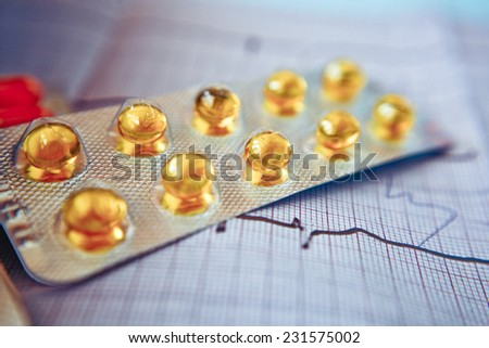 pills and capsules on the cardiogram - stock photo
