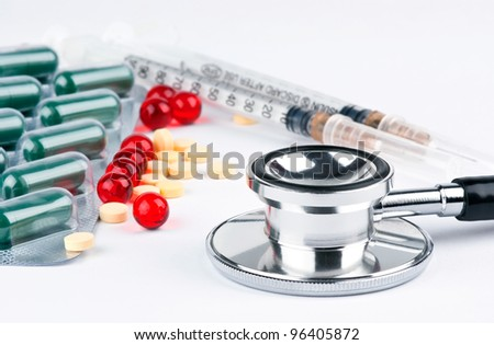 Pills and doctor's stethoscope on white background