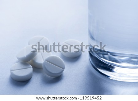 Pills and glass of water - stock photo