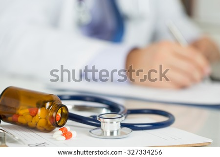 Pills and stethoscope laying on clipping board with prescription blank with male medicine doctor working on background. Medicine doctor's working table. Healthcare and medical concept. Copyspace - stock photo