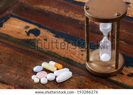 Pills and vintage hourglass on wooden table. Selective focus - stock photo