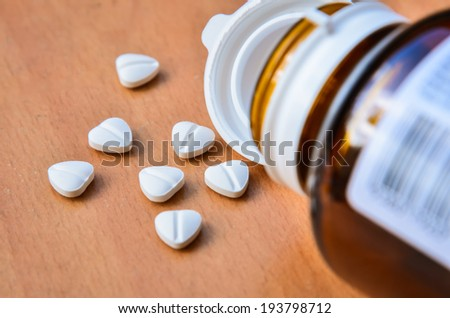 Pills as a heart on wood background