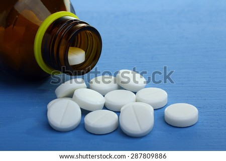 Pills from bottle on the blue background. - stock photo