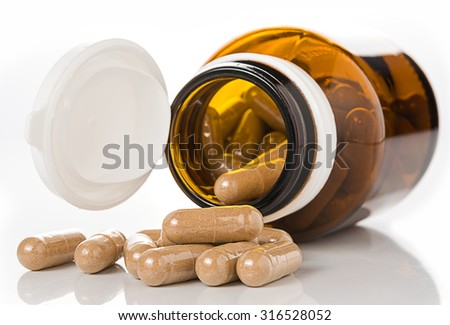 Pills from bottle on white background