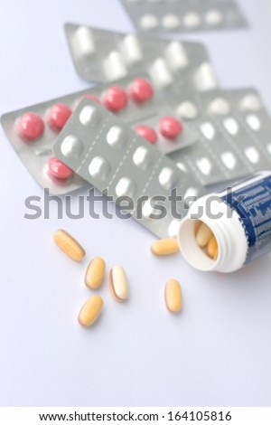 Pills in blister and pills in bottle, shallow DOF - stock photo