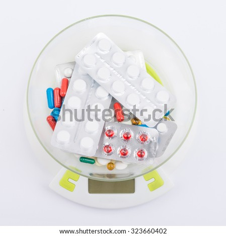 Pills in blister lying on an electronic balance. - stock photo