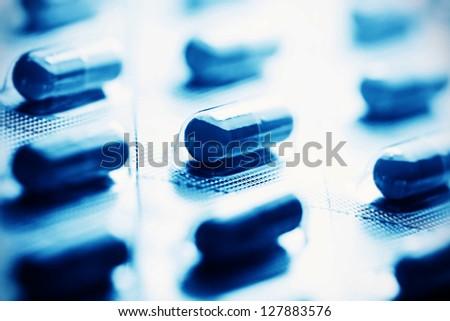 Pills in blue tone. Macro image. - stock photo