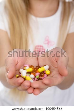 pills in kid hands. - stock photo