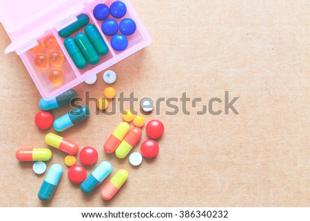 Pills in pink pillbox with clipping path on cardboard background