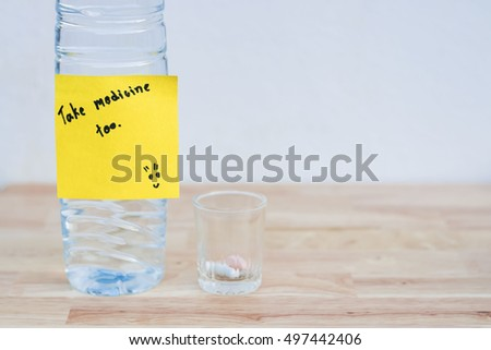 "Pills in small glass. And water bottle with message ""take medicine too"" on wooden floor. With copy space."
