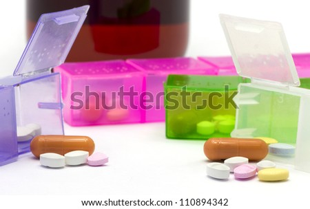 pills laying out of a box. In the back there's a bottle of syrup. - stock photo