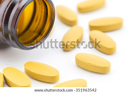Pills of vitamin C spilled out open container on white background. - stock photo