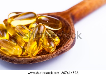 Pills on a spoon in white background.