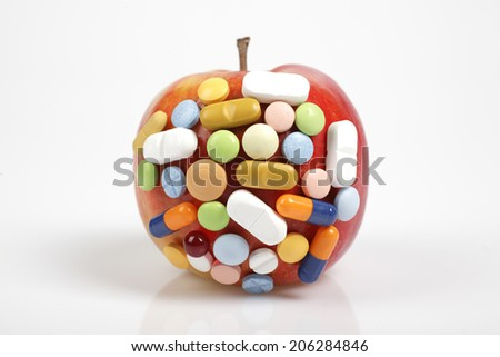 Pills on apple on white background symbolizing chemical contamination of food