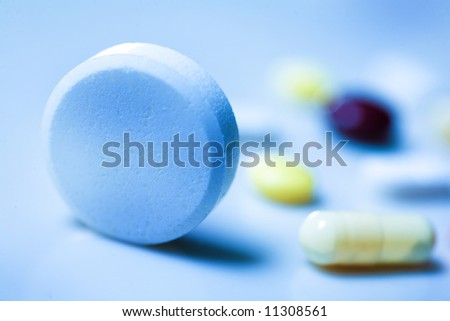Pills on blue background; Shallow depth of field. - stock photo