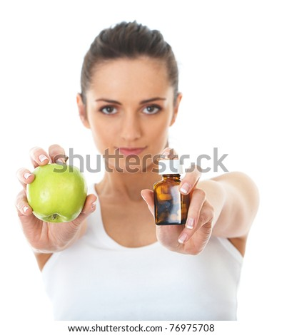 pills or fruits, attractive female holds vial with pills and green apple, choice from two sources of vitamins, isolated on white - stock photo