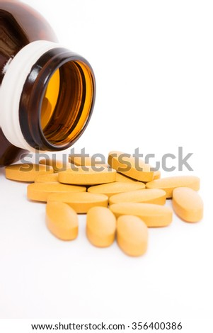 Pills pouring out of the brown medicine bottle  - stock photo