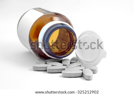 Pills pouring out of the glass brown bottle on white background - stock photo