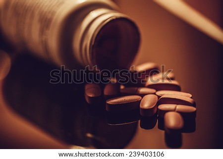 Pills scattered on a glass surface. Dark style. - stock photo