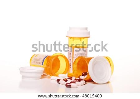 Pills spilled in front of prescription bottles - stock photo